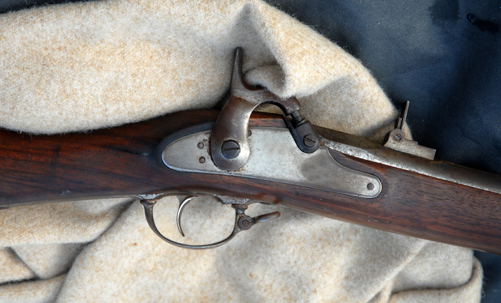 A closeup picture of the trigger and flintlock mechanism on a musket.
